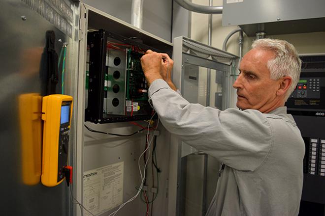 Team member testing electrical panel